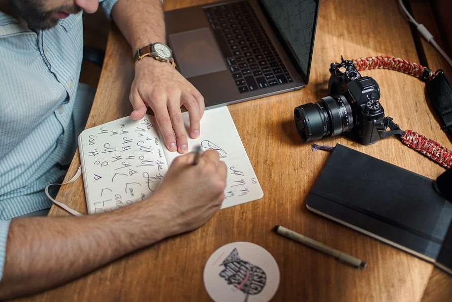 Man sketching in notepad with laptop and SLR camera in shot on wooden desk